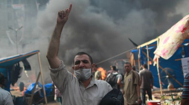 Cairo Burning: An Egyptian supporter of the Muslim Brotherhood gestures amid a ferocious army crackdown on protesters nationwide.