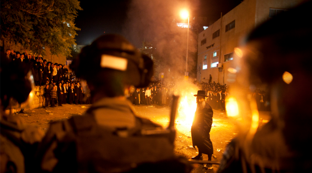 War in the Street: Ultra-Orthodox demonstrators set fires during a protest against Israeli government moves to scrap their exemption from national service.