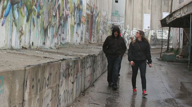 Wall of Injustice?: Tory Devries, right, of Santa Barbara, Calif., walks next to the Israeli-built separation barrier in Bethlehem.