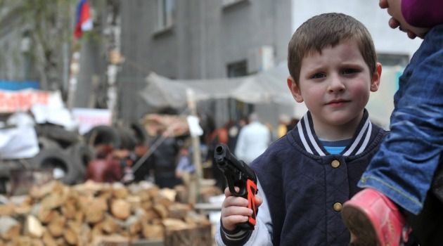 No Playing: A boy holds a toy pistol at a barricade outside the police regional building seized by the separatists in the eastern Ukrainian city of Slavyansk.