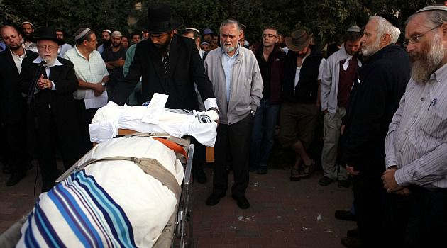 Solemn Moment: Jewish settlers gather for funeral of Asher Palmer and his son, Yonathan, whose car was hit by stone-throwing Palestinians on the occupied West Bank in 2011.
