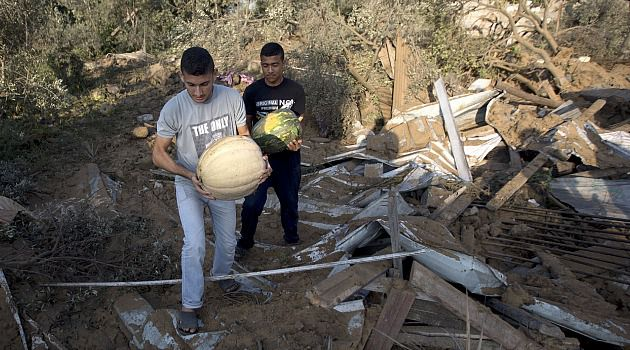 Melons Amid Madness: Palestinians carry melons through the wreckage of a home in Gaza town of Beit Hanoun.