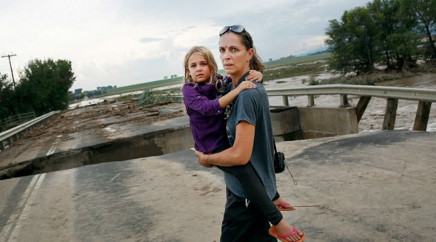 Rain, Go Away: Child clings to mother as they survey the remains of a flood-damaged road in Colorado.