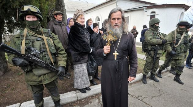 Crimean War? An Orthodox priest holds a crucifix as Russian soldiers patrol streets in the breakaway Ukraine region of Crimea.
