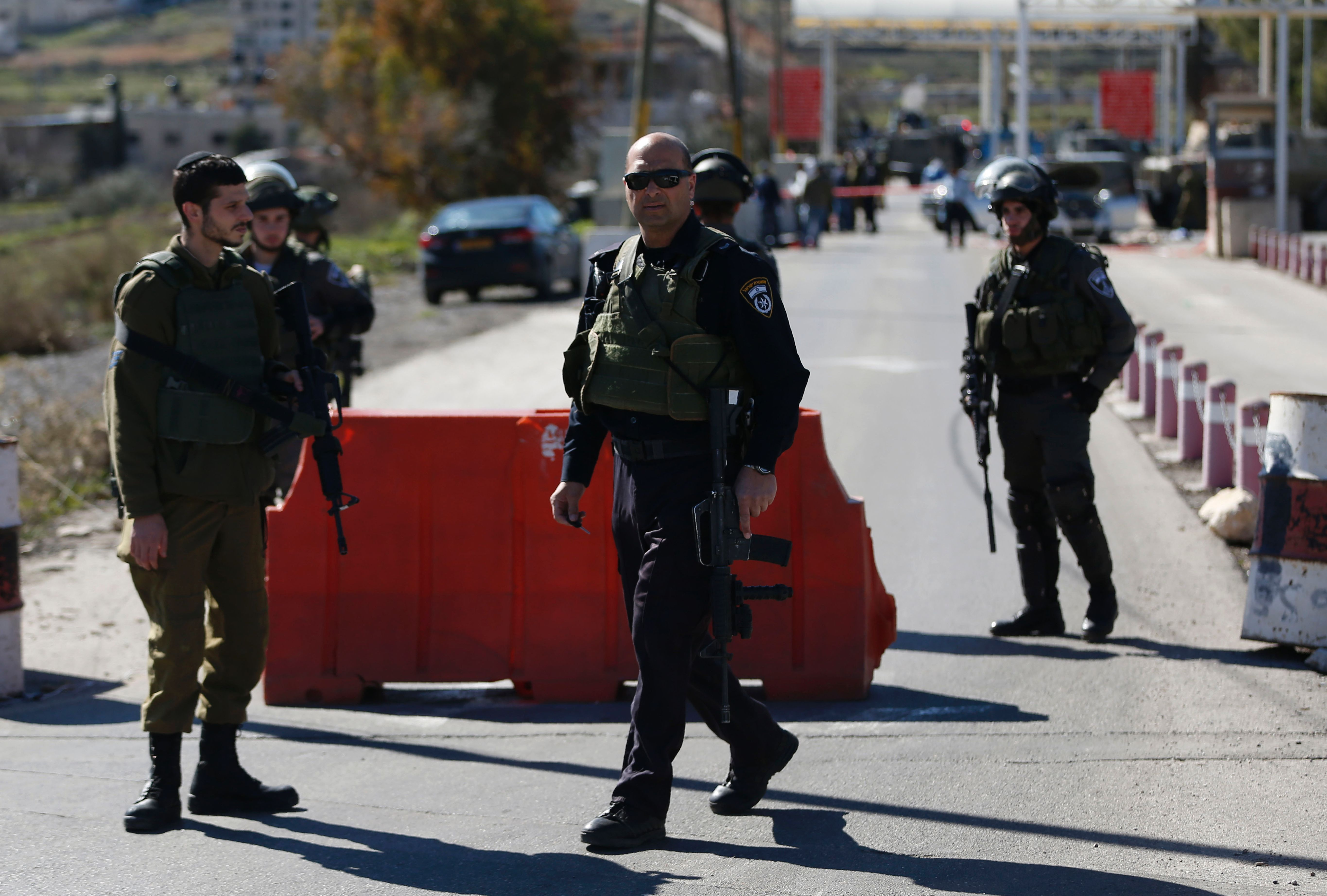 Israeli security forces secure the scene of a reported Palestinian shooting attack at a checkpoint near the Beit El settlement, close to West Bank city of Ramallah, on January 31, 2016.
