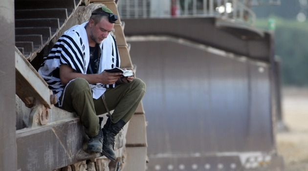 Gloves Off: Israeli soldier performs morning prayers as troops await orders near Gaza border.