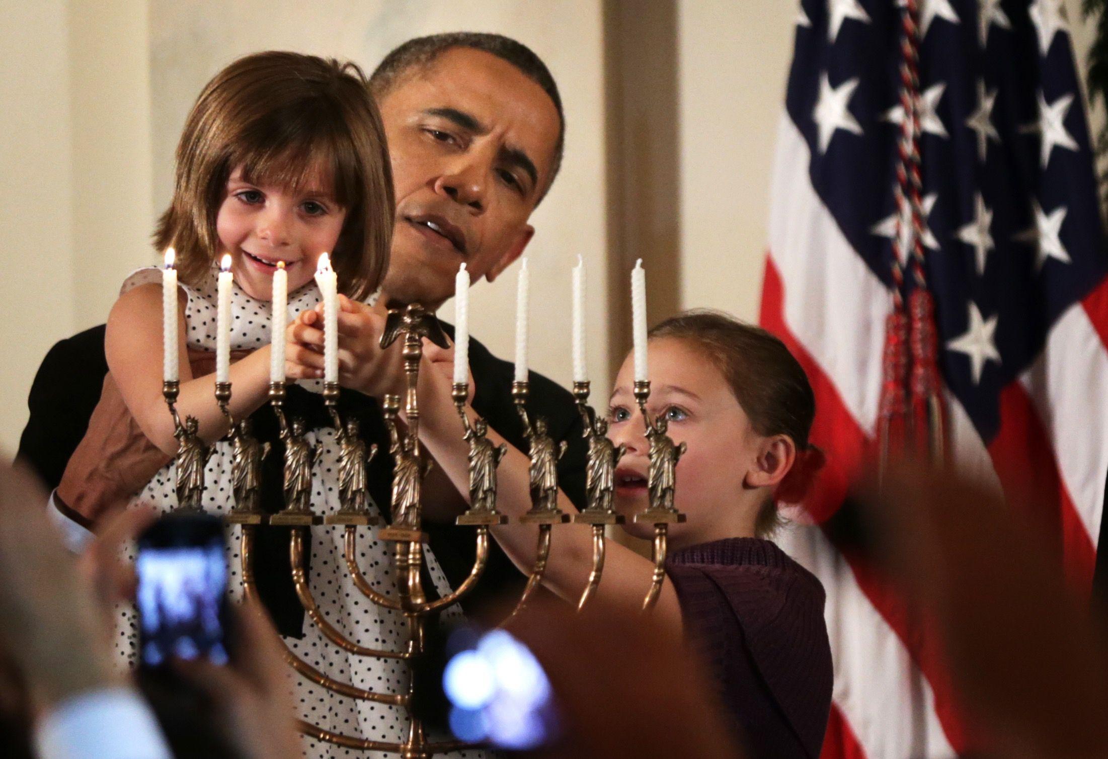 President Obama lights the menorah during the White House's 2014 Hanukkah celebration.