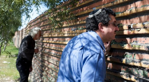 Rabbi Mark Diamond peers through a corrugated-iron wall along the border with Mexico. The American Jewish Committee leader is part of a nearly unprecendented push by Jewish groups for immigration reform