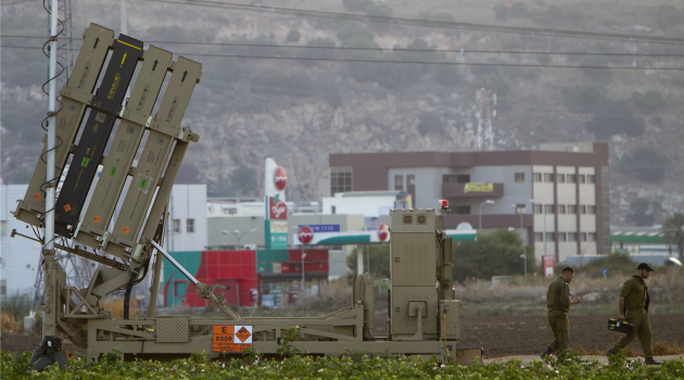 Tension Rising: Israeli soldiers walk past the Iron Dome missile defense system. Several rockets from Lebanon hit the north of the country Sunday in the latest sign of escalating tension.