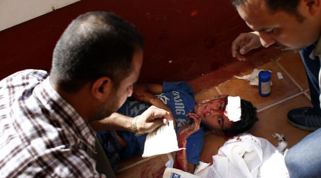 Humane Scribes: Journalists help Palestinian boy wounded during Israeli shelling that killed four boys on a Gaza beach.