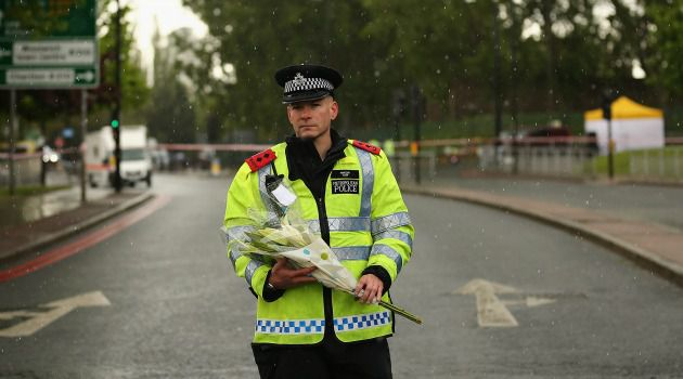 Flowers and Hate: A London policeman stands guard during a hail storm near the scene of the deadly meat cleaver attack on a soldier by a self-proclaimed Islamist.