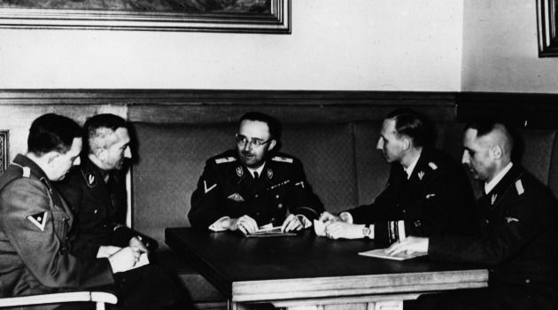 Dark Days: Gestapo boss Heinrich Muller, second from left, listens to briefing from fellow Nazis.