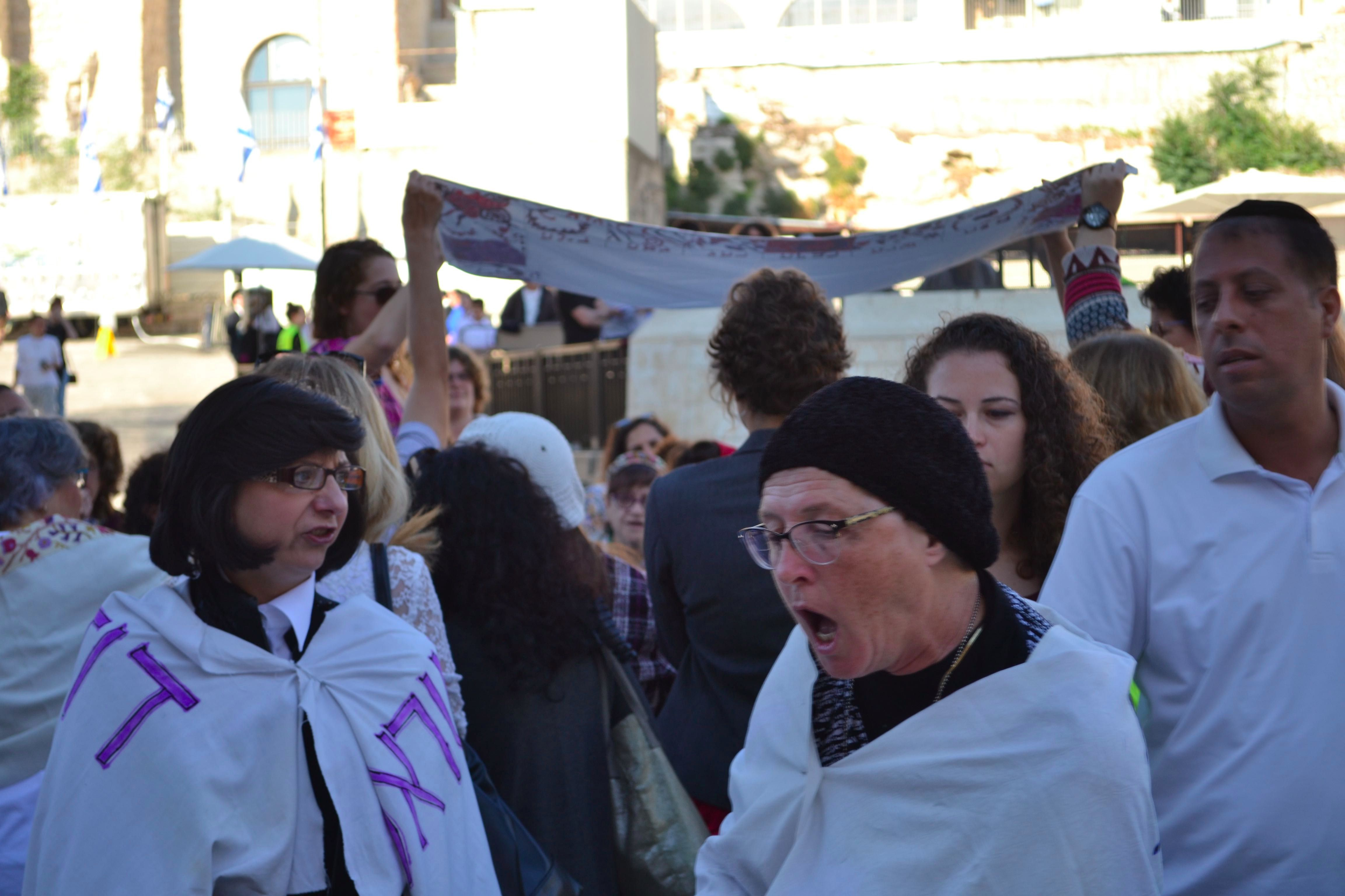 Ultra-Orthodox women wrapped in protest signs yell as Women of the Wall conducts a bat mitzvah in the background on September 4.