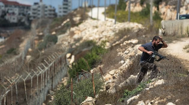 Safe? An Israeli soldier inspects a fence surrounding the settlement of Psagot in Octovber after a Palestinian intruder stabbed a 9-year-old girl.