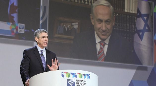 Speaking to Flock : Rabbi Rick Jacobs addresses the Union for Reform Judaism?s biennial conference, as Israeli Prime Minister Benjamin Netanyahu appeared on a big screen video link.