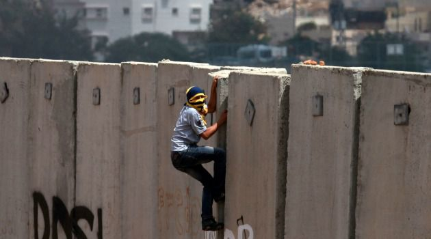 Occupation Drama: Palestinian protester climbs the Israeli separation wall near a West Bank Jewish settlement.
