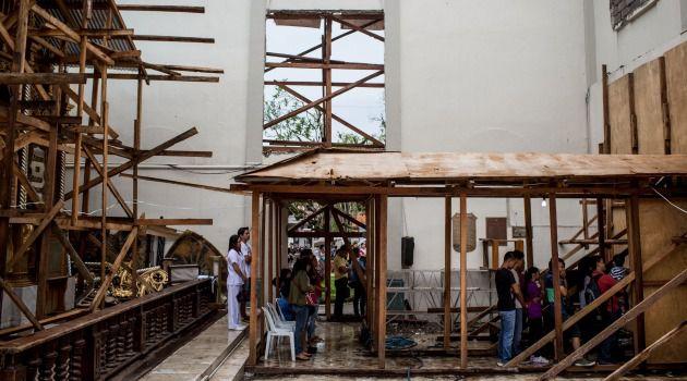Praying for Help: Filipino survivors of Typhoon Haiyan worship in damaged church.