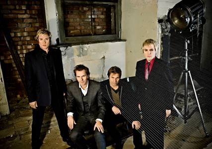 Duran Duran sit in a fancy living room and there's a little graphic art on one side of the photo