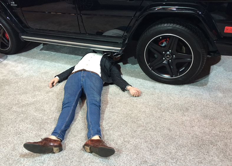 man under car at the New York Auto Show