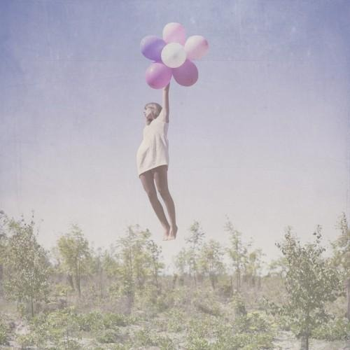 girl floating in air holding balloons