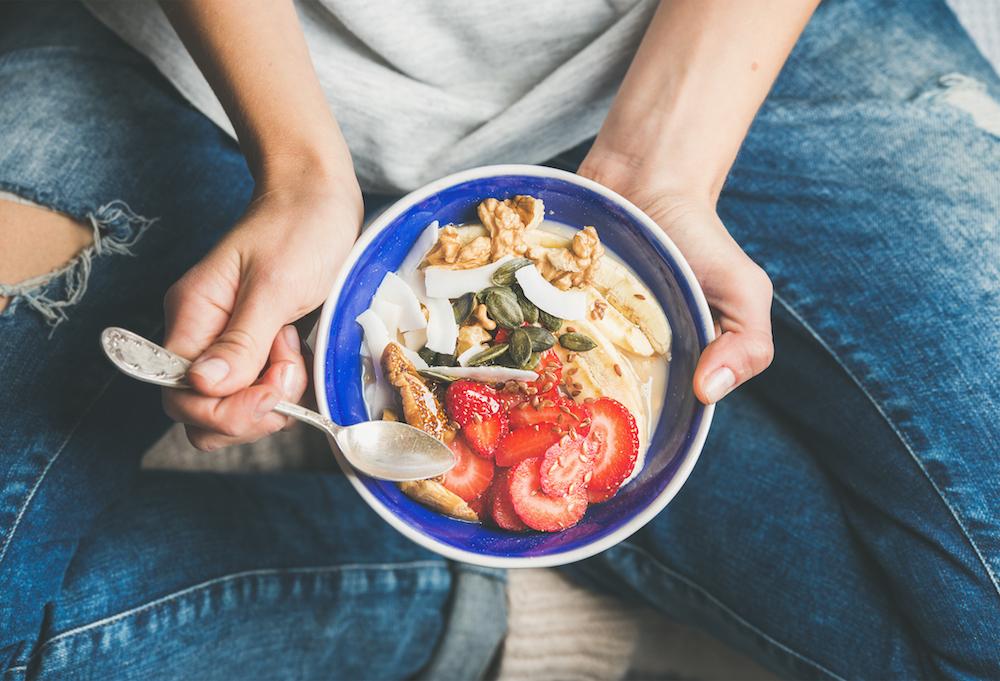 Healthy breakfast bowl, yogurt, granola, seeds, coconut, strawberries, fruit