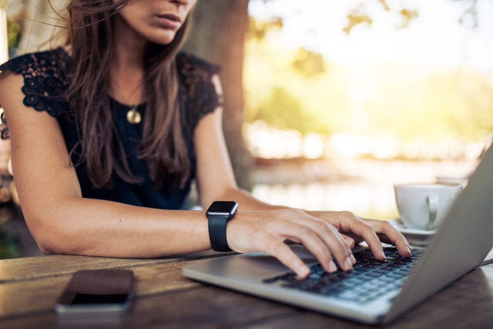 Woman working on laptop with coffee smart watch