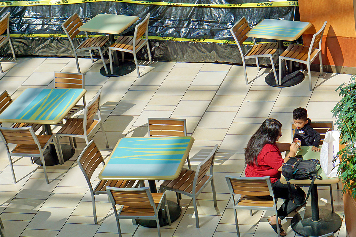 A mother and child share a treat in the virus-modified food court at Park Plaza in Little Rock.