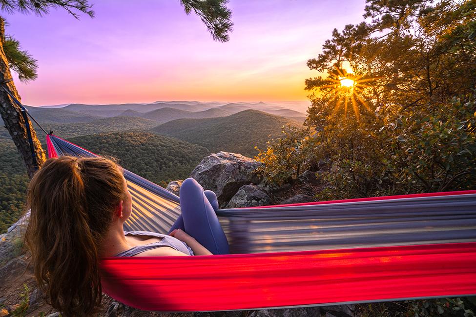 woman in hammock looks at sun over hills 135167