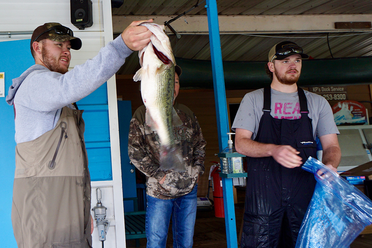 Hunter Thomas, left, was the winner of Holiday Island's Big Bass Tournament this month, hauling in a 4.8-pounder to win a $3,000 first prize.