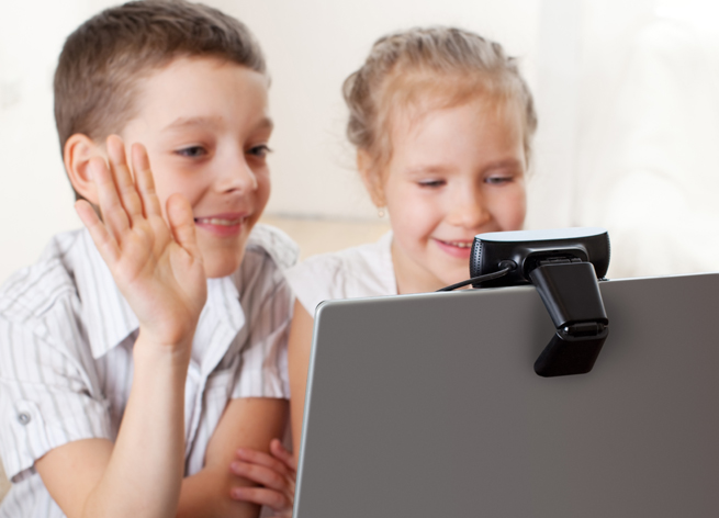 children looking at computer monitor skype