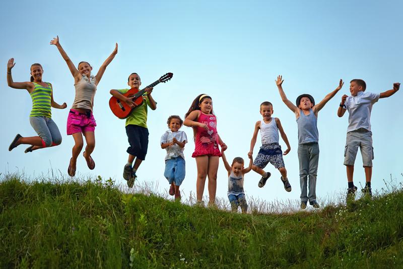 summer camp kids jumping grass