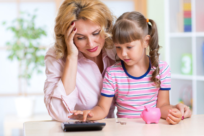 Young girl with older woman learning finance calculator budget