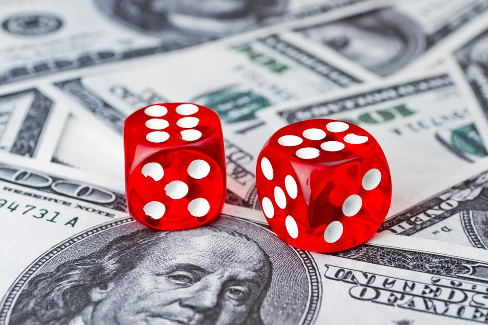 Red_Dice_Laying_On_Money