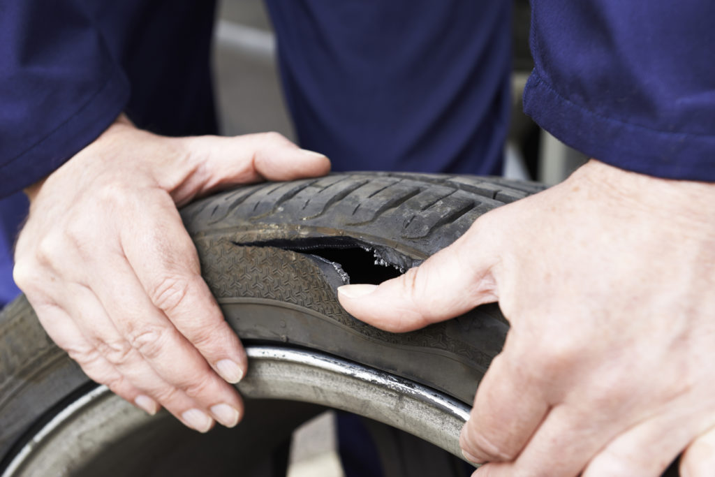 Close Up Of Mechanic Examining Damaged Car Tire