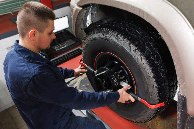 Mechanic performing a wheel alignment.