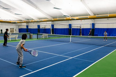 Teenagers playing doubles tennis at PBA Tennis Center