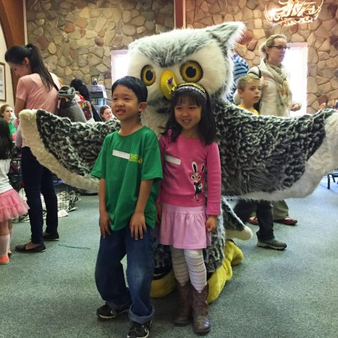 Two children stand in front of Otis the Owl (mascot) at Meadowside Nature Center for the Annual Egg Hunt (2016)