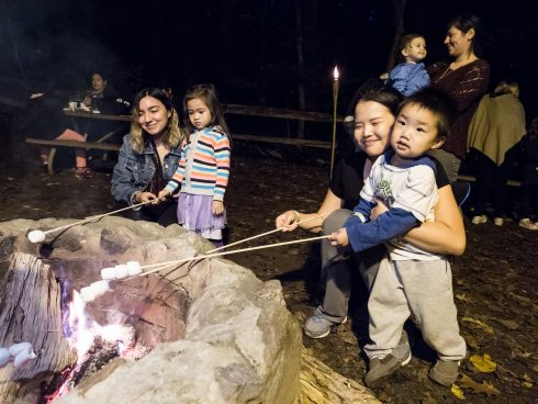 Young children at campfire with their parnets