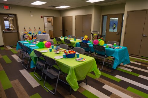The Wheaton Indoor Tennis Party Room, available for rent, is decorated for a party with balloons and colorful tablecloths