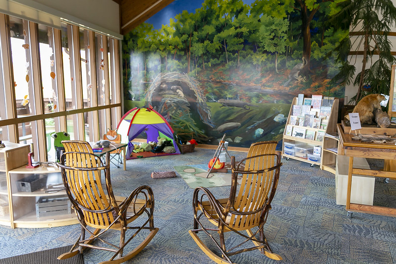 Photo of inside of Black HIll Visitor Center with rocking chairs and childrens activity corner