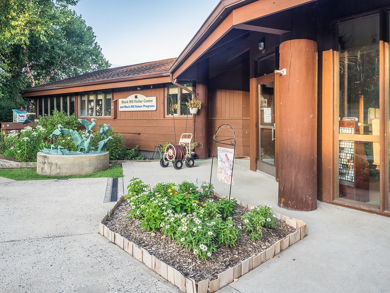 Close-up photo of Black Hill Visitor Center at the front door with flower beds