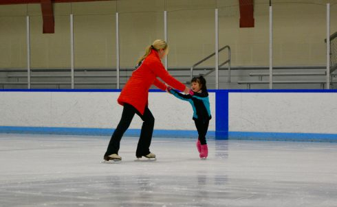 A young girl is instructed on how to turn during a 2016 figure skating camp