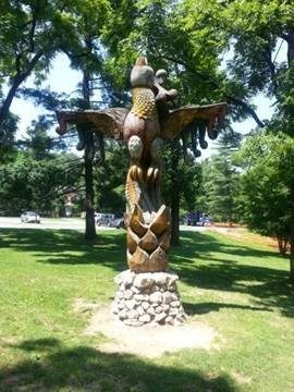 Layhill Phoenix- wood carved sculpture of a totem pole featuring a phoenix rising from columns of flames.