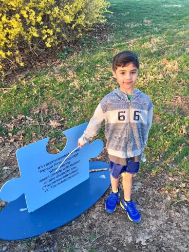Boy standing next to Autism Awareness sign