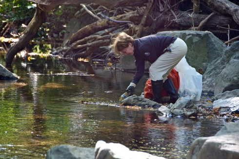 Women picking up trash from a stream