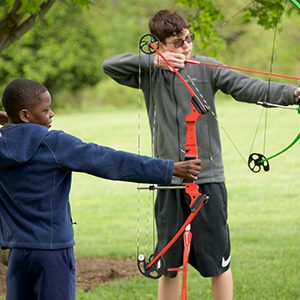 Two kids shooting arrows
