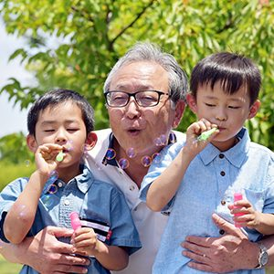 Two children blowing bubbles with an older gentleman holding them