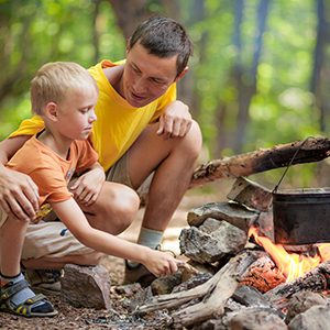 Father and son at campfire in woods