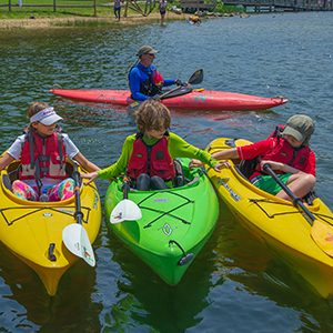 Three kayaks lined up with children inside holding hands