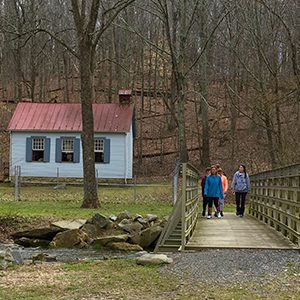 a group walking over a bridge with a small building in background
